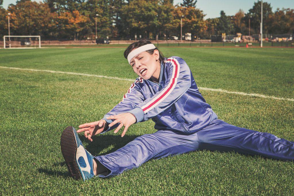 Stretchübungen auf dem Sportplatz, Aufwärmen